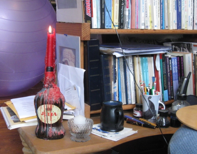 My tool table: candles, pens, ink bottles, blotter.