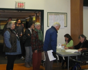 Voters check in with the registrars as they enter the gym. IDs are not required. You'd have a hard time passing yourself off as anyone else, and unless you can clone yourself, you can't vote twice.