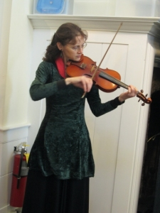 A fiddler strolled up and down the aisles, entertaining us with her music. (Name TK.)