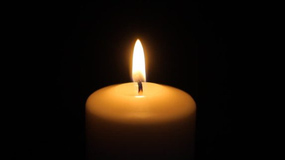 lit white candle in darkness